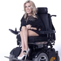 Dr. Danielle Sheypuk in a power wheelchair, smiling