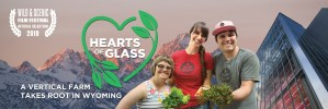 Three employees at Vertical Harvest holding plants in front of the greenhouse and mountains. Text: Hearts of Glass A Vertical Farm Takes Root in Wyoming