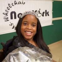 Katrina Hazell wearing a crown in front of a banner for Miss Wheelchair New York
