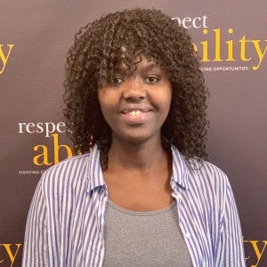 Angelique Uwabera smiling in front of the RespectAbility banner