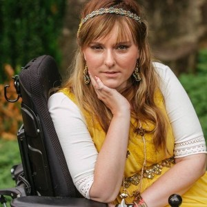 Ariella Barker in front of a tree and bushes. Ariella is a wheelchair user