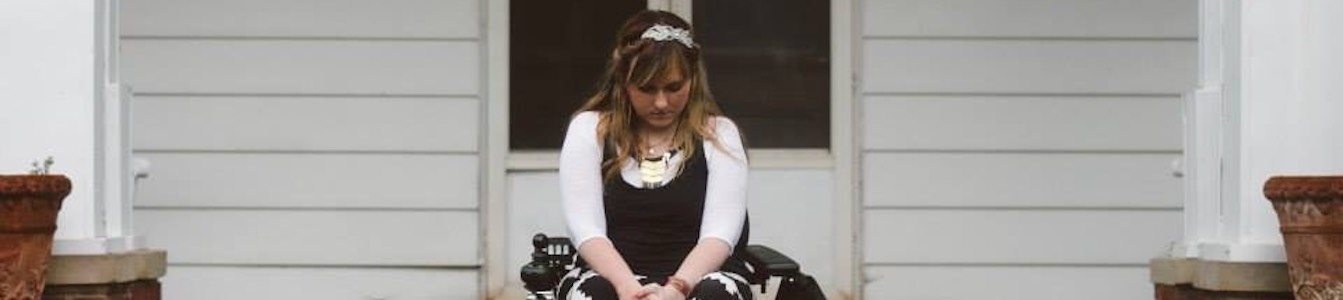 Ariella Barker sitting in a wheelchair in front of her house, looking down