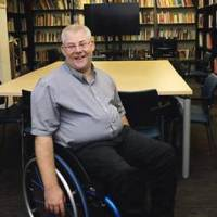 Yoav Kraiem smiling in front of shelves of books and a TV. Yoav is a wheelchair user