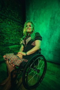 Ali Stroker smiling in front of green walls