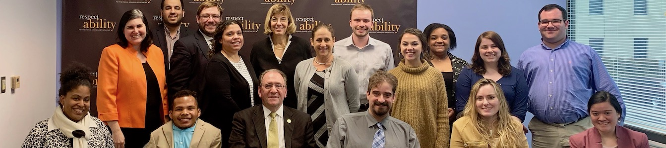 Neil Romano with RespectAbility staff and Fellows in front of the RespectAbility banner