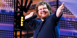 Ryan Niemiller on stage on America's Got Talent. Niemiller has a disability in both of his arms.