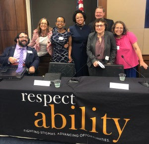 Self Advocacy Panelists at the 2019 RespectAbility Summit smile together behind a table with RespectAbility's logo on it