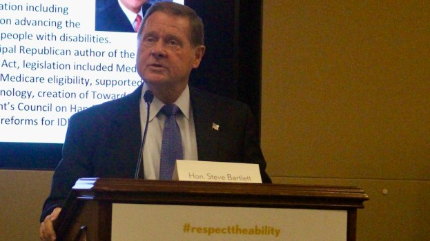 Steve Bartlett speaking in front of a screen with his biography on it behind a podium with #RespectTheAbility on it