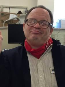 Doug Jarett smiling wearing a red bandana around his neck.