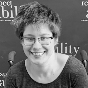 Otilia Lampman smiling in front of the RespectAbility banner