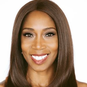 Andrea Jennings smiling in front of a white backdrop