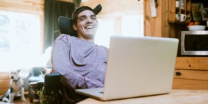 A young man who uses a wheelchair sits behind a laptop with the rest of his apartment blurred in the background