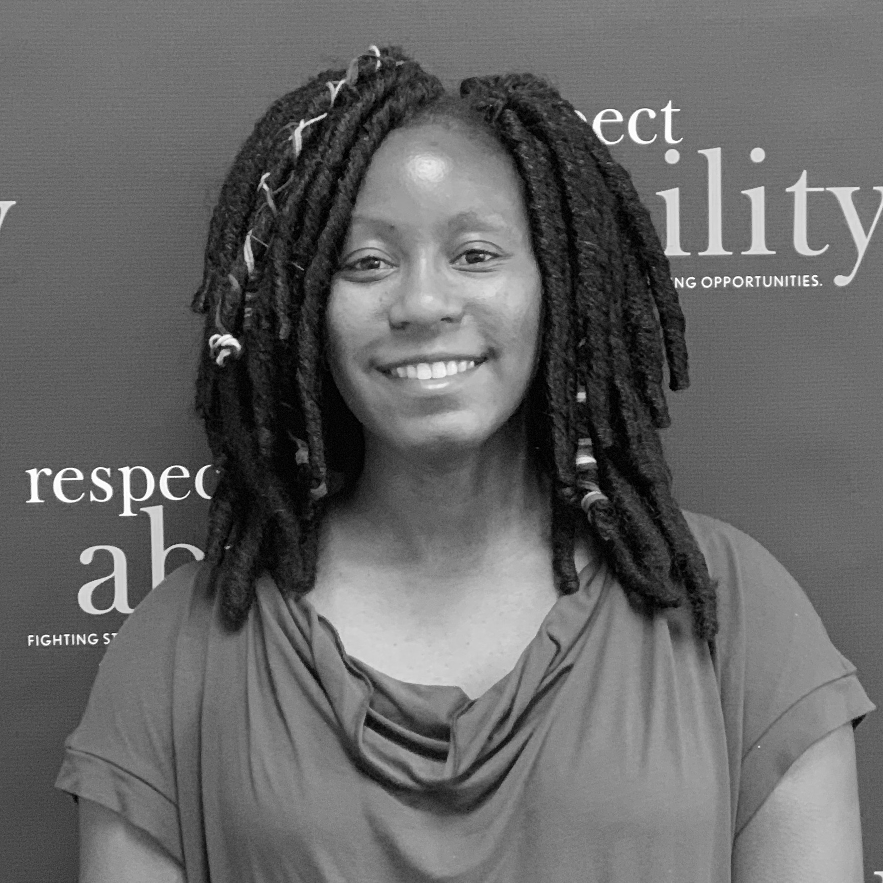 Courtney Murray smiling in front of the RespectAbility banner