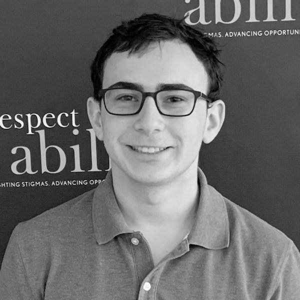 Eitan Jacobsohn smiling in front of the RespectAbility banner