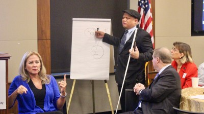 Ollie Cantos writing on a flip chart holding a large white cane, as Jennifer Laszlo Mizrahi and Steve Bartlett look on seated at a table. Sign language interpreter is in the lower left of the frame. American flag in the background