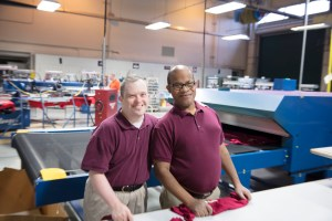 Two Bank of America Support Services employees smiling together inside a t-shirt factory