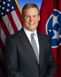 Tennessee Governor Bill Lee smiling in front of the state flag and an American flag