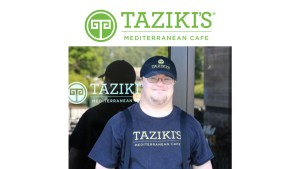 A worker with a disability standing outside Taziki's Mediterranean Cafe wearing a hat and shirt with the restaurant's logo on it. Taziki's Mediterranean Cafe logo.