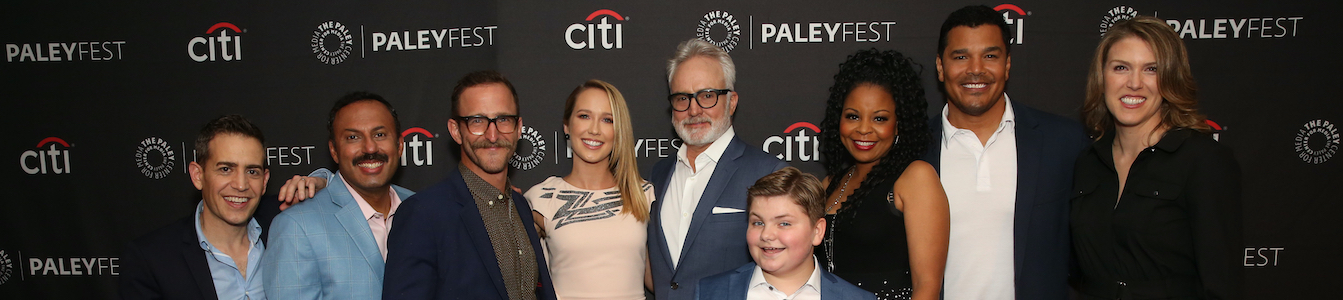The cast of NBC's Perfect Harmony smiling together in front of logos for Citi and Paleyfest