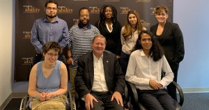 Rep. Steve Bartlett with RespectAbility Fall 2019 Fellows smiling in front of the RespectAbility banner