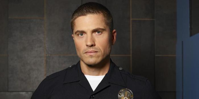 Eric Winter as Tim Bradford wearing a police uniform with badge on The Rookie