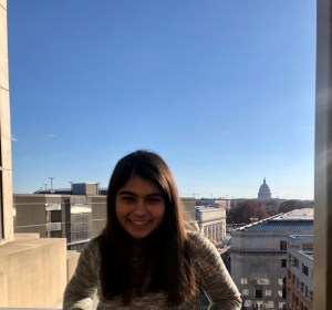 Sneha smiling with the US capitol in the background