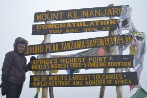 Sneha standing at the top of Mount Kilimanjaro with multiple signs behind her