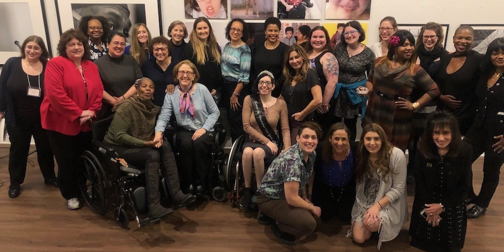 Women with disabilities smile together inside Positive Exposure's art gallery in New York City