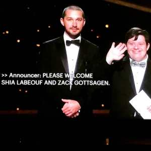 Zack Gottsagen presenting with Shia LeBeouf on stage at the 2020 Academy Awards with captions on screen