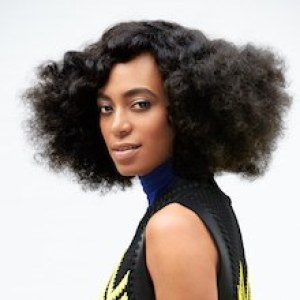 Solange Knowles wearing a black and yellow dress smiling for the camera