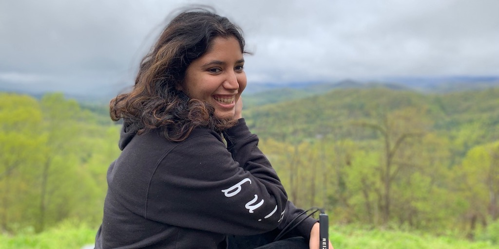 Baksha Ali smiling holding her white cane with a large forest in the distance behind her