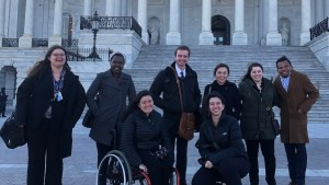 RespectAbility Fellows with disabilities and allies smile together in front of the U.S. Capitol building steps