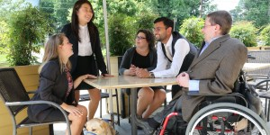 RespectAbility Fellows with disabilities around a table outside, having a conversation