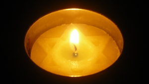 A lit Yom Hashoah candle in a dark room on Yom Hashoah