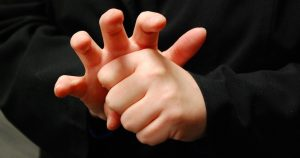 The American Sign Language word for COVID-19 mimics the virus' appearance, with fingers forming the spikes, or coronas, the virus is known for. Photo credit: NCDHHS.