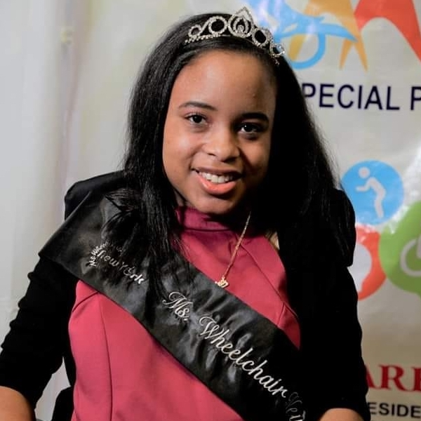 Ketrina Hazell headshot smiling wearing a sash that says Ms. Wheelchair New York on it