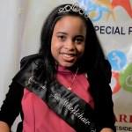 Ketrina Hazell headshot smiling wearing a sash that says Ms. Wheelchair New York on it