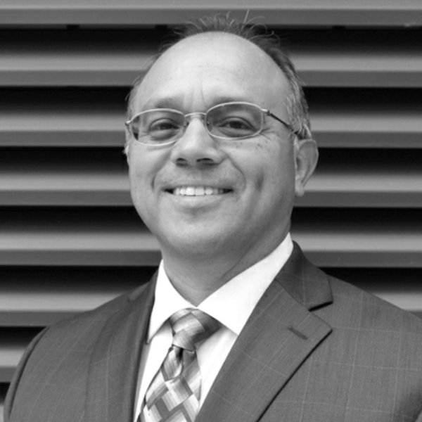 Jaime Pacheco Orozco smiling wearing a suit and tie and glasses. Jaime has short black hair