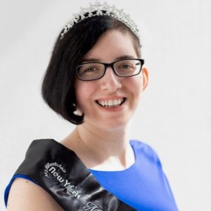 Lauren Arena headshot smiling wearing a sash that says Ms. Wheelchair New York on it