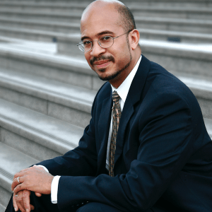 Stephen David Simon sitting on a stone staircase wearing a suit and tie and glasses.