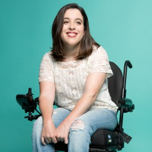 Anastasia Somoza smiling. Somoza is a white woman with brown hair down to her shoulders who uses a power wheelchair. She is seated in front of a green backdrop
