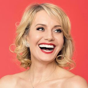 Eileen Grubba headshot smiling in front of a red backdrop. Grubba is a white woman with short blonde hair