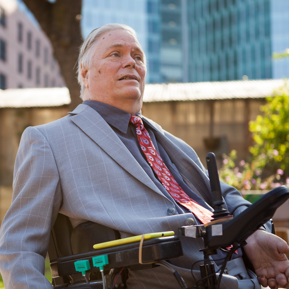 Lex Frieden smiling wearing a suit and tie. Frieden uses a power wheelchair.