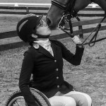Alanna Flax-Clark with a horse kissing her face. Flax-Clark is a wheelchair user.