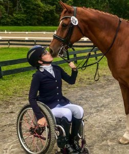 Alanna Flax-Clark with a horse kissing her face. Flax-Clark is a wheelchair user.