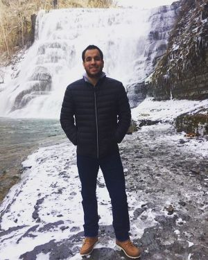 Franklin Anderson smiling, standing in front of a waterfall