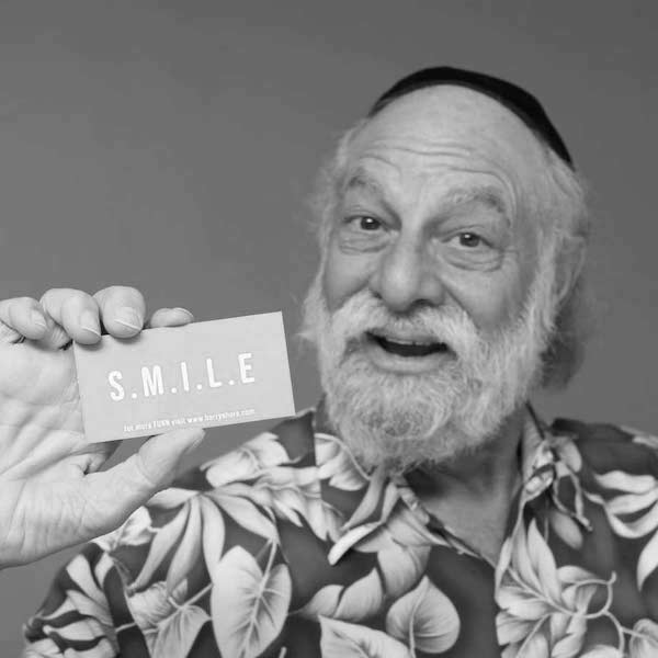 Barry Shore smiling holding up his business card with the word SMILE on it.