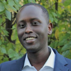 Headshot of Ian Cherutich smiling in front of trees and bushes.