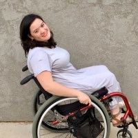 Cami Howe smiling leaning back in her wheelchair