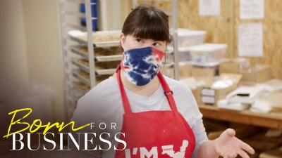 Collette Divitto in her bakery wearing a mask and apron in a scene from Born For Business. Show logo in bottom left